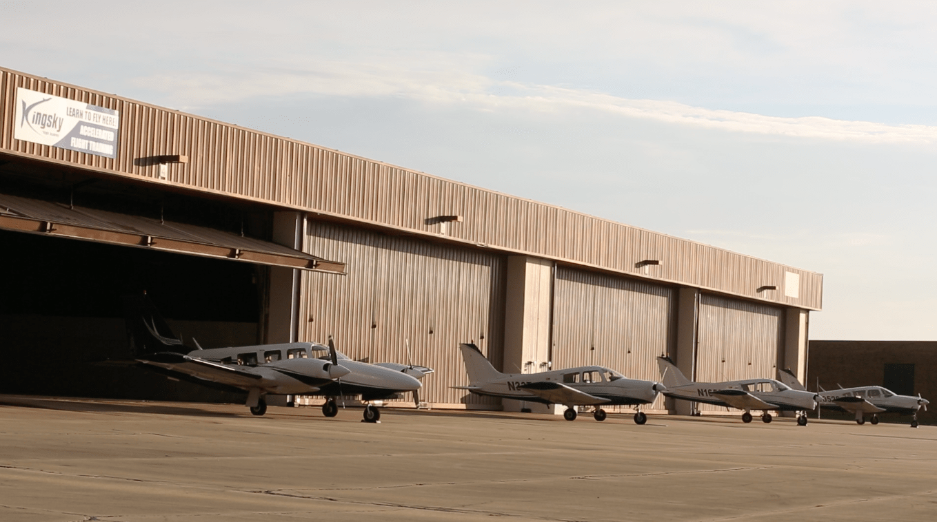 airplanes standing in a row front of kingsky flight academy